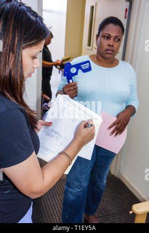 Miami Florida Liberty City Jessie Trice Community Health Center fair free care exam volunteer Black Hispanic woman ophthalmology - Stock Image
