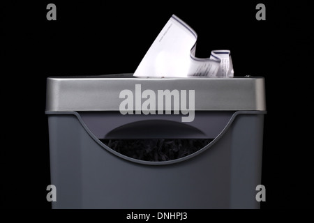 A close-up view of a paper shredder with paper going inside. - Stock Image