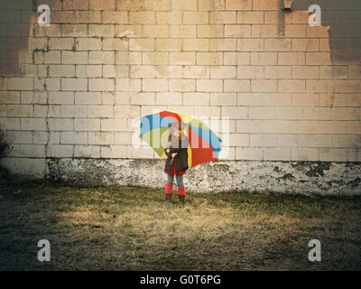 A little child is standing against a brick wall holding a rainbow umbrella outside for a hope, peace or creative - Stock Image
