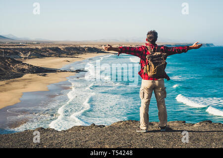 Alone happy traveler with backpack people man enjoying the destination place beach standing on a cliff and opening arms for success and joyful concept - Stock Image