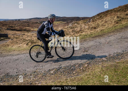 Mature male cyclist riding up a gravel track close to Poolewe, west coast of Scotland. - Stock Image