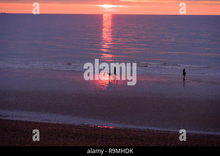 Hastings,  East Sussex, UK. 26th Dec, 2018. Boxing Day walkers get a brief glimpse of the sun at sunrise on the beach, on a mild but overcast day on the south coast. - Stock Image