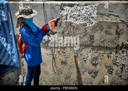 Thailand female construction worker, woman builder drilling concrete wall - Stock Image