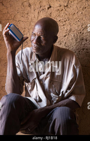 Samba village, Yako Province, Burkina Faso: A house-holder listens to an educational radio programme on nutrition broadcast by the local Natigmbzanga Radio. - Stock Image