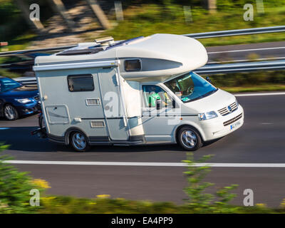 Camper van speeding down a motorway. A getaway. Motion blur used to give a sense of speed. - Stock Image