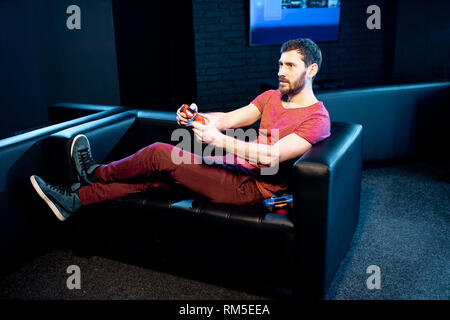 Man playing video games with gaming console and joy stick sitting on the couch in the dark room of the playing club - Stock Image