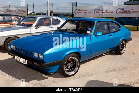 Three-quarters front view of a Blue, 1984  Ford Capri, in the Intentional Paddock, at the 2019 Silverstone Classic Media Day - Stock Image