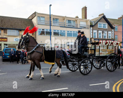 A funeral in the North of England with a traditional hearse drawn by two black horses - Stock Image