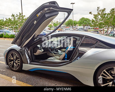 BMW i8 plug in hybrid super car or sports car parked at the curb with driver's door open showing the cockpit of the hybrid electric automobile in USA. - Stock Image