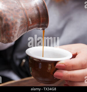 Pouring hot coffee in a ceramic cup with a traditional Turkish copper coffee pot. - Stock Image