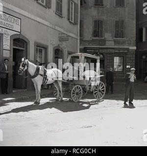 1950s, historical picture, summertime and a tourist open-air horse and cart waiting for passengers in a square in Gibraltar infront of the retail store of Bassadone & Co, bakers and confectioners. - Stock Image