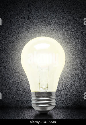 Glowing electrical incandescent light bulb isolated on asphalt background with copy space. - Stock Image