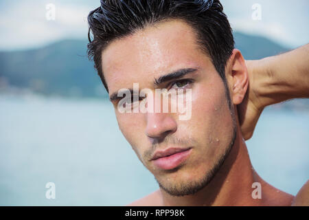 Handsome young man getting out of water with wet hair - Stock Image