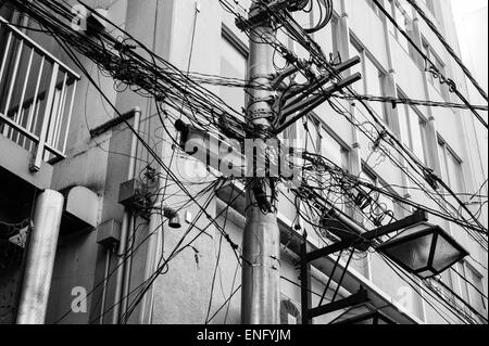 Overhead cables and wires in the street in Tokyo - Stock Image