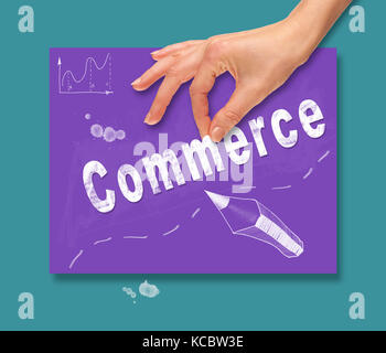 A hand picking up a Commerce concept on a colorful drawing board. - Stock Image