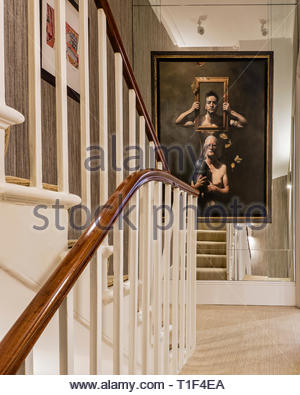 Painting of men on mirrored wall by staircase - Stock Image