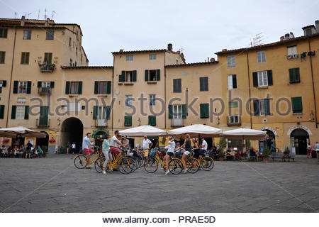 Cycling tour group meet in the centre of the Piazza dell Anfiteatro: Lucca, Italy. - Stock Image