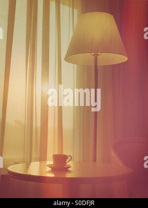 Hotel room sunrise scene featuring coffee cup, table, floor lamp, chair and curtains with vintage bokeh overlay. - Stock Image