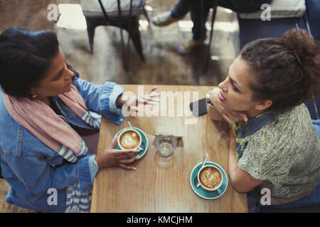 Young women friends talking and drinking cappuccinos at cafe table - Stock Image