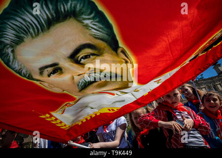 A pioneer holds a red banner with a portrait of Joseph Stalin on the Red Square of Moscow during the pioneers meeting, Russia, May 19, 2019 - Stock Image