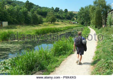 A man walks alongside the disused Thames & Severn Canal, in Thrupp near Stroud, Gloucestershire, UK. - Stock Image