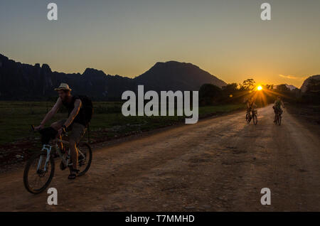 Tourists cycle in around the countryside of Vang Vieng, Laos - Stock Image