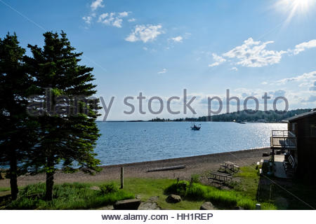 A sailboat is anchored in Grand Marais Harbor on the north shore of Lake Superior, Minnesota, Sawtooth Mountains - Stock Image