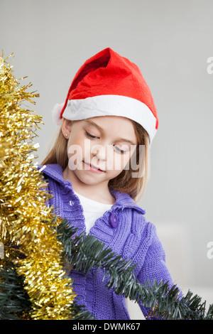 Girl Looking At Tinsels During Christmas - Stock Image