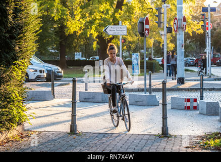 Strasbourg, Alsace, France, young woman bicycling on pavement, late afternoon light, - Stock Image