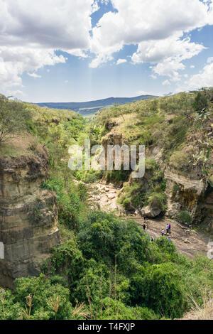 Ol Njorowa gorge with people walking on the dry river bed, Hells Gate National Park, Kenya - Stock Image