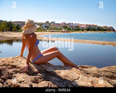 Woman enjoying the sun at the beach on Platanes Beach, Thasos - Stock Image