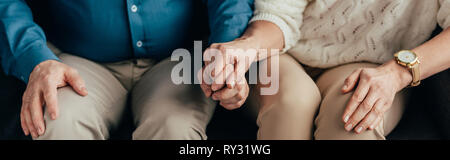 cropped view of couple holding hands while sitting at home - Stock Image