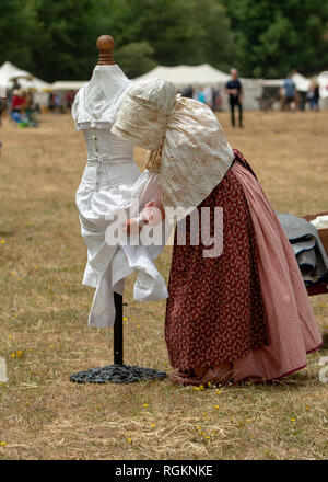 Duncan Mills, CA - July 14, 2018: Lady dressed in costume arrangng undergarments at a civil war re-enactement. The Civil War Days is one of the larges - Stock Image