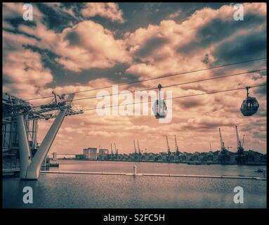 Two cable car pods of the Emirates Air Line Cable Car transport system depart & arrive at the Royal Victoria Docks terminal. This iconic transport system traverses the River Thames in London, England. - Stock Image