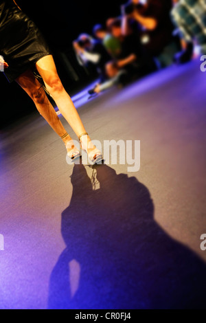 Woman walking down the catwalk at the fashion show - Stock Image