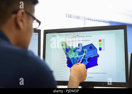 Engineer designing gearboxes using computer aided design (CAD) software in gearbox factory - Stock Image