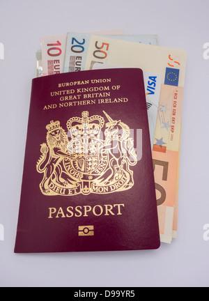 Euro banknotes and a Visa Credit Card inside of a British passport. - Stock Image