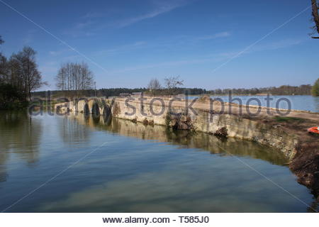 An old brick bridge with 3 arches, built across a lake in the beautiful Suffolk countryside on a bright spring day in England - Stock Image