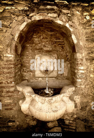 An old drinking fountain in the main street of Macharaviaya, a municipality in the province of Málaga in the mountains of the autonomous community of  - Stock Image