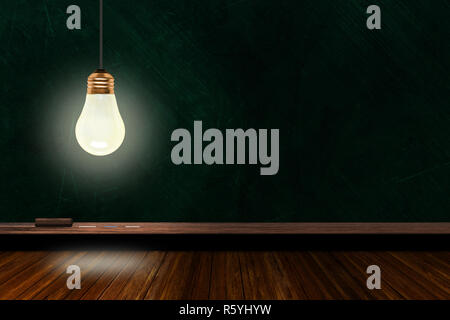 Hanging and illuminated light bulb in a classroom with background chalk board and wooden table and copy space. Concept of ideas, creativity and innova - Stock Image
