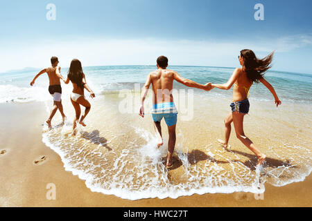 Happy group of friends runs to sea - Stock Image
