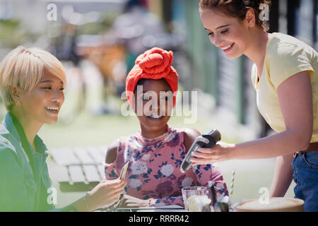 Young woman paying waitress with credit card at sunny sidewalk cafe - Stock Image