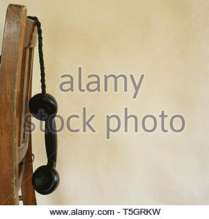 Telephone handset hanging over the back of a wooden chair. - Stock Image