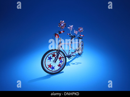 A twin seated bicycle with red white a blue decorations on a blue background. - Stock Image