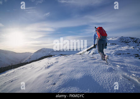 Hiker walking through the snow along Hartsop Above How that leads towards Hart Crag. English Lake District. - Stock Image