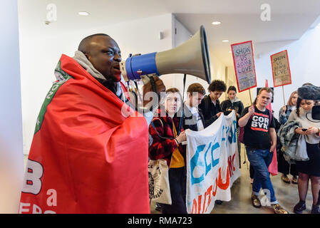 London, UK. 14th February 2019.Independent Workers Union of Great Britain's (IWGB) Security Guards and Receptionists branch chair Michael Bukola speaks in the foyer of the Ben Pimlott buidling at the launch their campaign for Goldmsiths, University of London, to directly employ its security officers. Currently they are employed by CIS Security Ltd on low pay and minimal conditions of service, and CIS routinely flouts its legal responsibilities on statutory sick pay and holidays. Credit: Peter Marshall/Alamy Live News - Stock Image