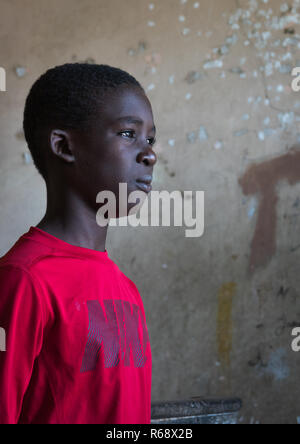 Young man inside his home, an old portuguese colonial building, Namibe Province, Namibe, Angola - Stock Image