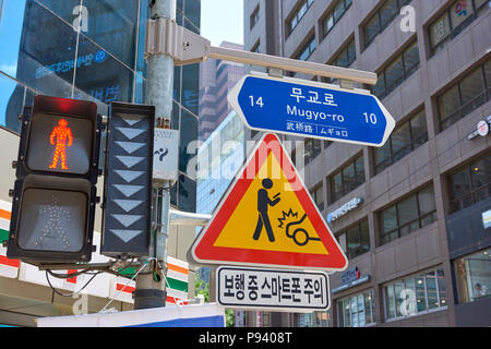 Detail of traffic sign in Seoul, South Korea, warning drivers to look out for distracted mobile phone users crossing the street. - Stock Image