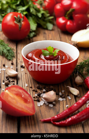 Sauce ketchup in a red cup, fresh tomato, pepper, green herbs and spices on a wooden background - Stock Image
