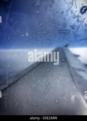 View over wing of passenger aeroplane, dramatic treatment, scratched, frosted window. - Stock Image